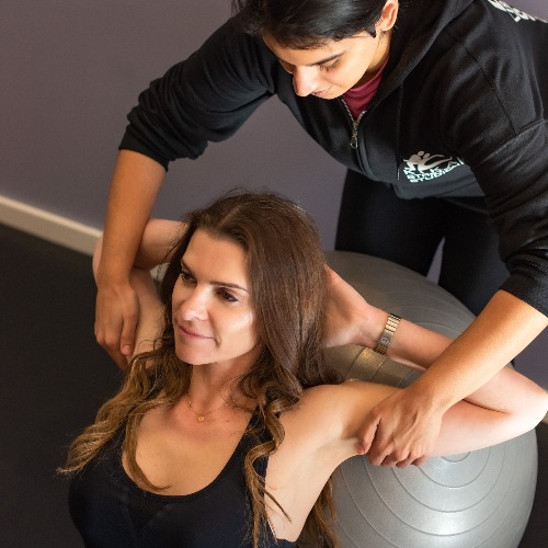 Stretching Client on Medicine Ball